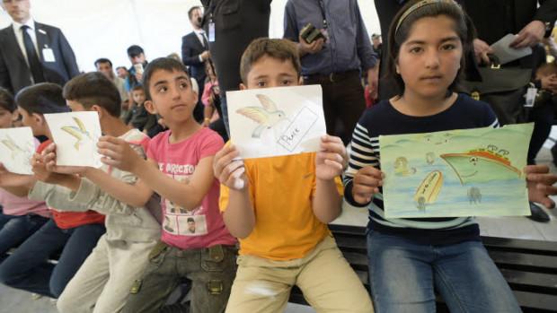 16 avril 2016 : Enfants réfugiés montrant des dessins lors de la visite du pape François, dans le camp de Moria à Lesbos (Grèce).