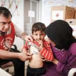 Au Liban, une mère et son fils, réfugiés syriens, consultent dans une unité médicale mobile.