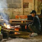 """Un migrant prépare la cuisine dans le camp de """"Vietnam City"""" à Angres (Pas-de-Calais)."""
