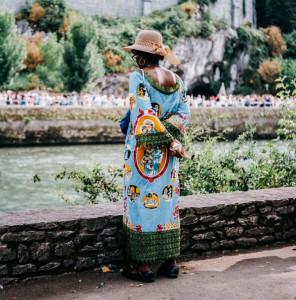 Une femme portant une tenue traditionnelle africaine à l'effigie de Saint Antoine de Padoue prie en face de la grotte de Massabielle, de l'autre côté du Gave, durant le pèlerinage National de l'Assomption à Lourdes.