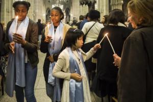 20 avril 2019 : Les servantes d'assemblée, qui portent une écharpe de couleur bleu, transmettent la lumière aux fidèles, lors de la Vigile pascale. Paroisse Saint-Jean-Baptiste de Belleville, Paris (75), France.